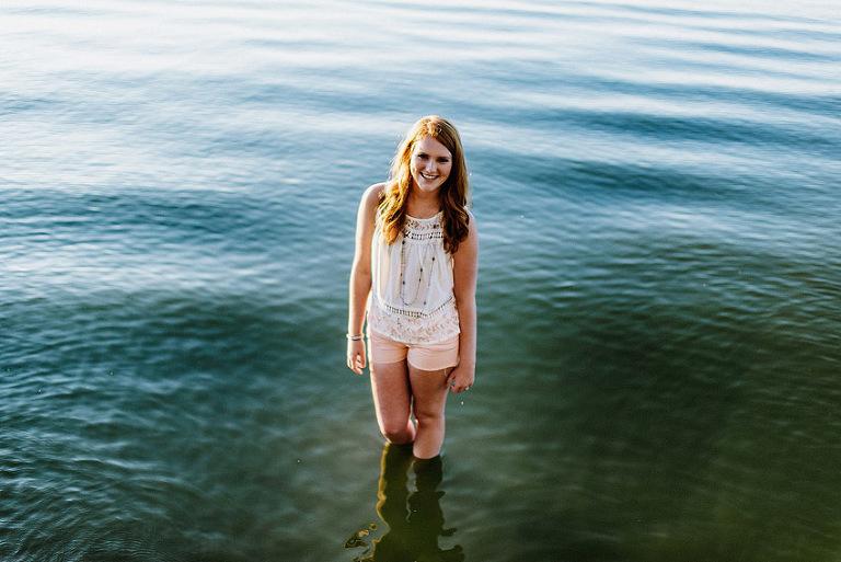 senior girl standing in a lake