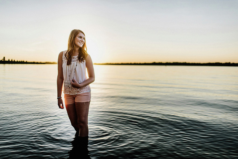 senior girl standing in a lake at sunset with ripples
