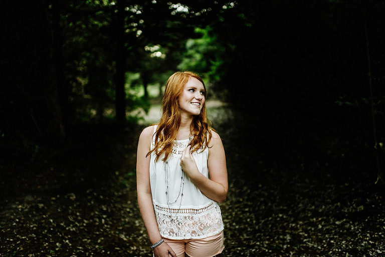 redhead senior girl standing in the woods