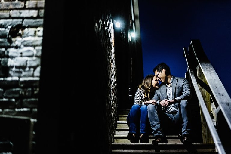 sitting and holding hands at night on some stairs