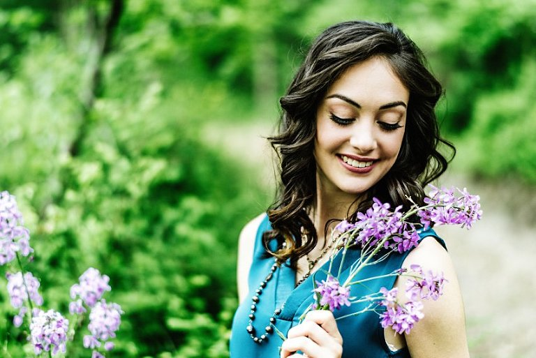 girl in white pants and a blue top looking at the purple flowers she's holding