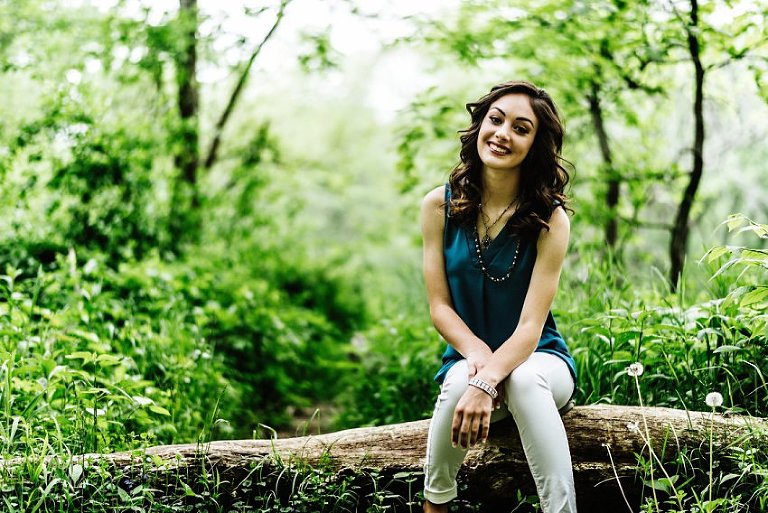 girl in white pants and a blue top sitting on a log in the forest
