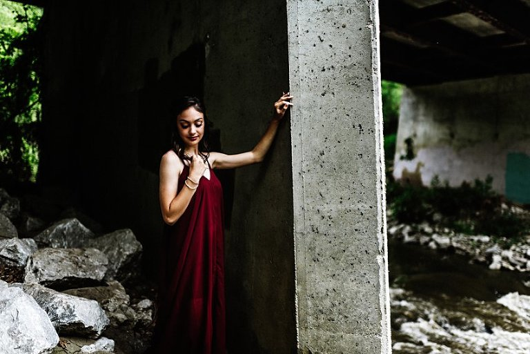 girl standing and looking at the rocks below under a concrete bridge
