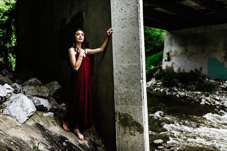 girl standing and looking off into the distance under a concrete bridge