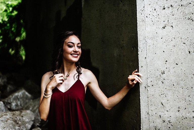 girl standing smiling under a concrete bridge