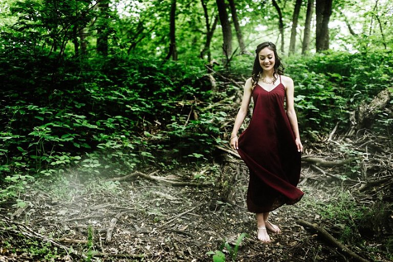 smiling girl in the woods with light behind her while she swings her dress with smoke on the ground