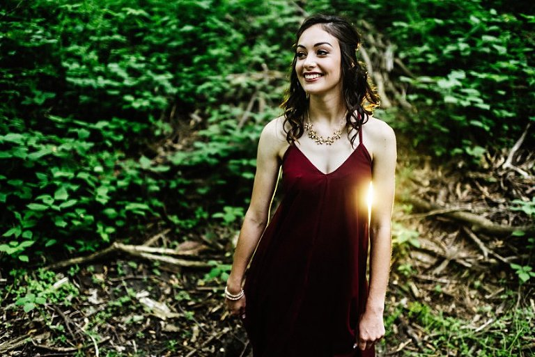 smiling girl in the woods with light behind her