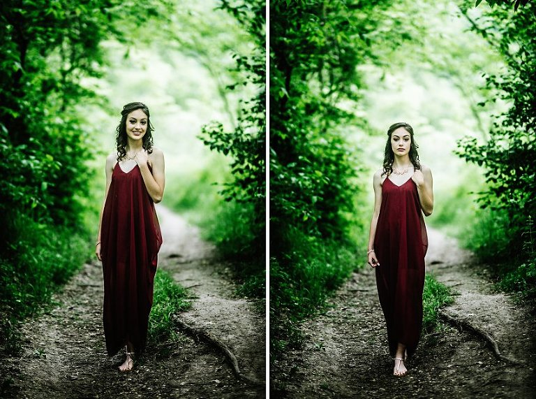 girl in a red dress standing on a path in the woods with trees that make a tunnel