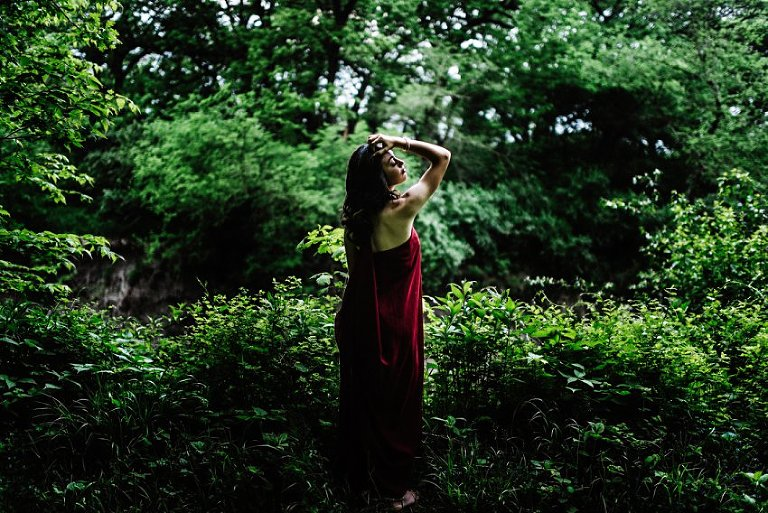 full length photo of a girl in a forest clearing looking very serious off camera with her hand in her hair