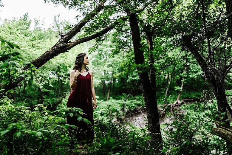 girl in a red dress looking off camera in a dramatic view of the woods