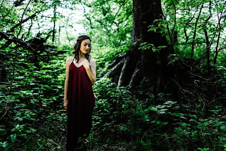 girl standing in dramatic light in front of tree roots holding her necklace