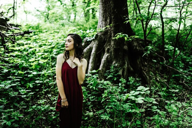 girl standing in front of tree roots holding her necklace