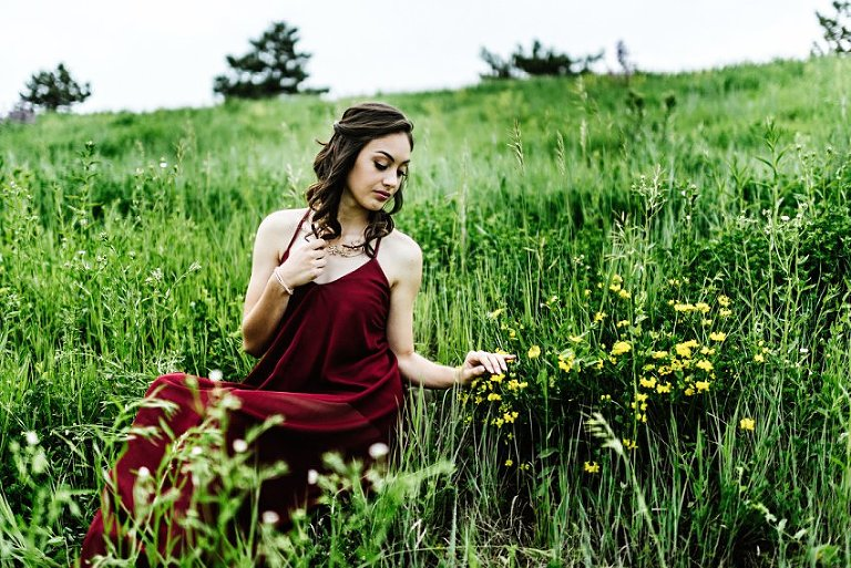 a girl in a red dress sitting in a field touching flowers
