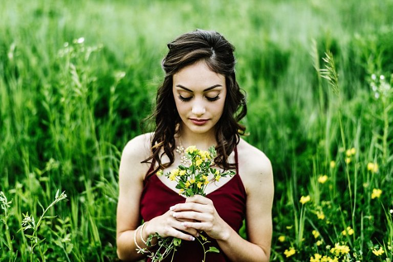 a girl in a red dress sitting in a field looking at flowers