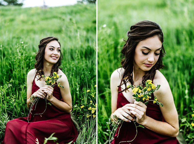 a girl in a red dress sitting in a field holding flowers