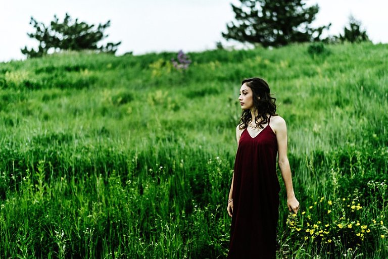 a girl in a red dress standing in a field