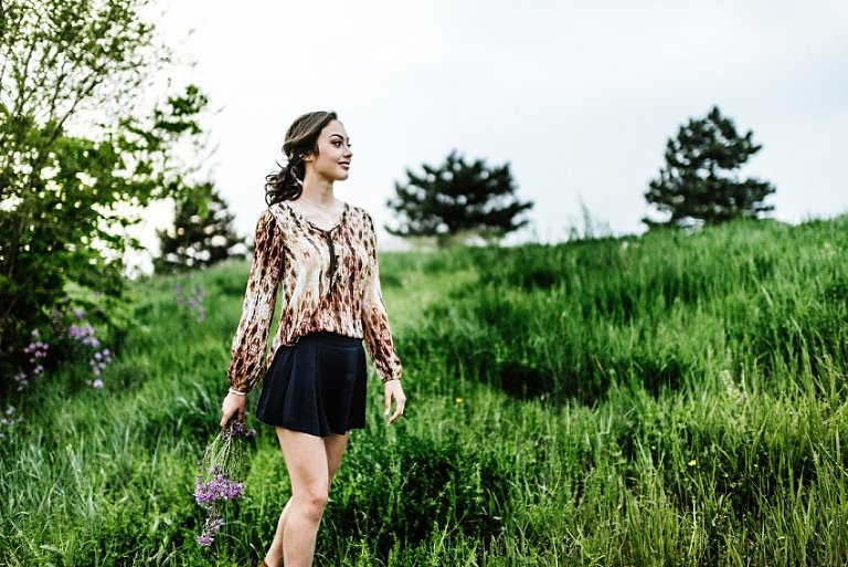 a girl walking through a field of grass and flowers