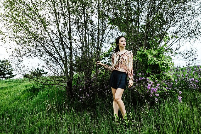 full length photo of a girl standing in front of a tree and flowers