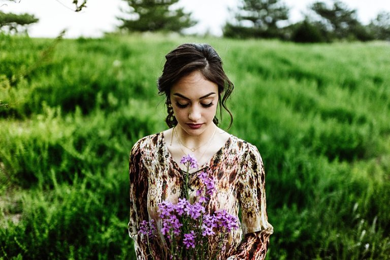 girl in a field looking down at purple flowers