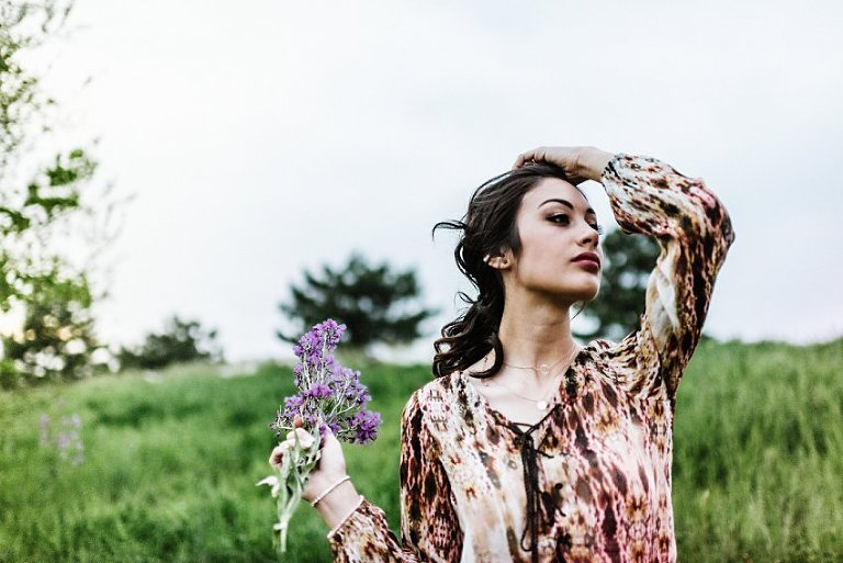 girl holding flowers and pulling her hair back in the wind