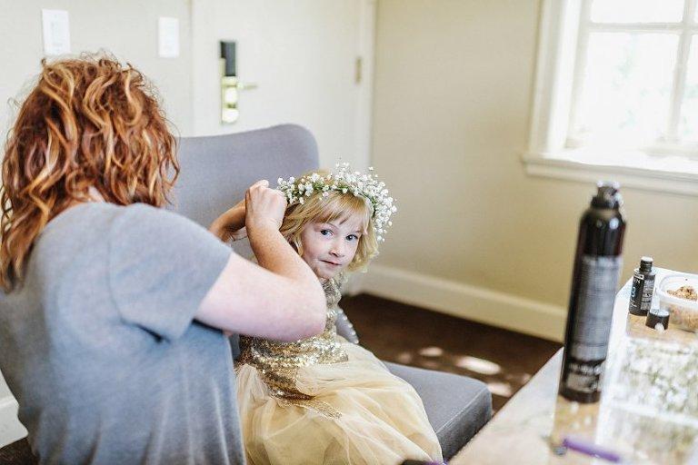 the flower girl having her flower crown put on her head