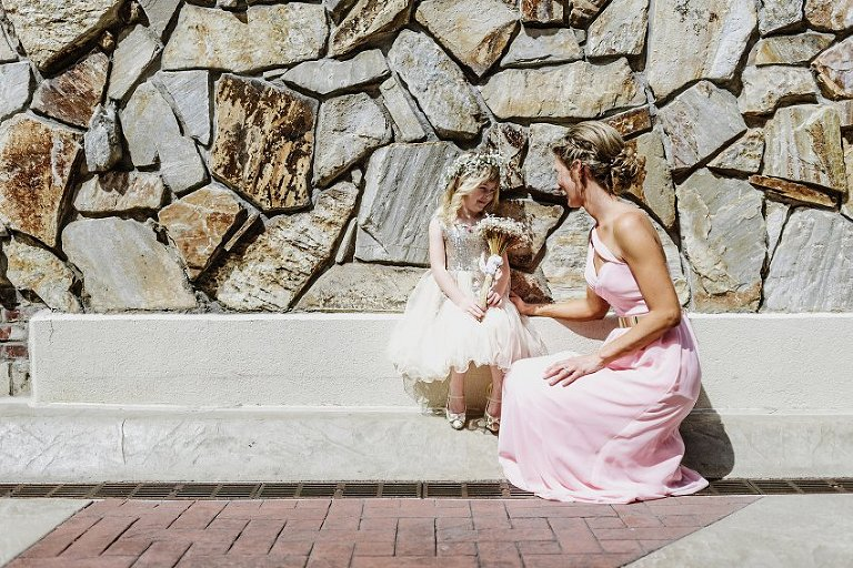 a bridesmaid and the flower girl smiling at each other