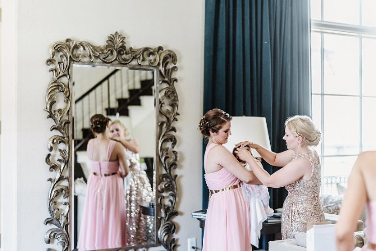 baby getting her hair adjusted by bridesmaids