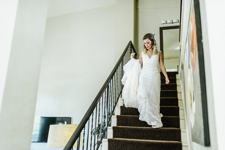 the bride walking down the stairs after putting on her dress
