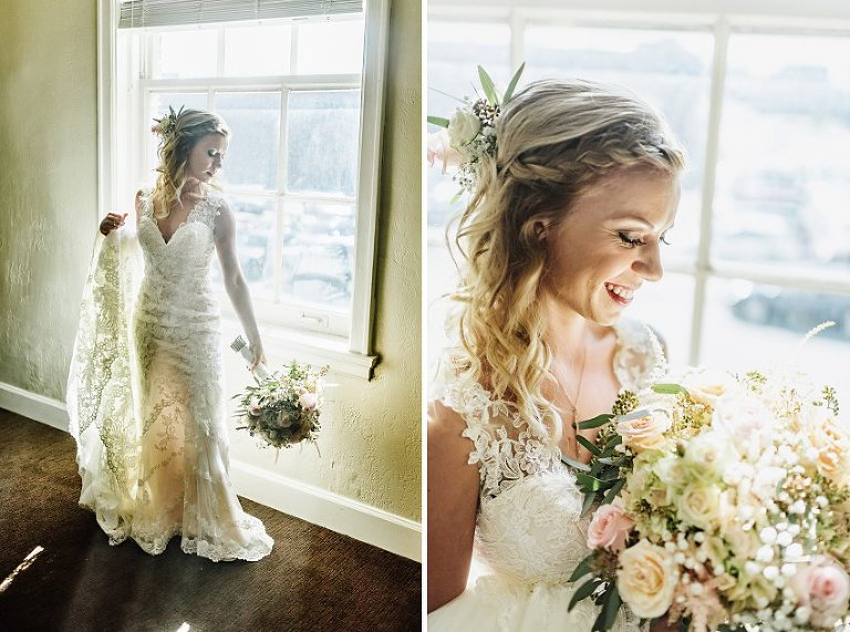 the bride standing in front of a sunlit window with her flowers