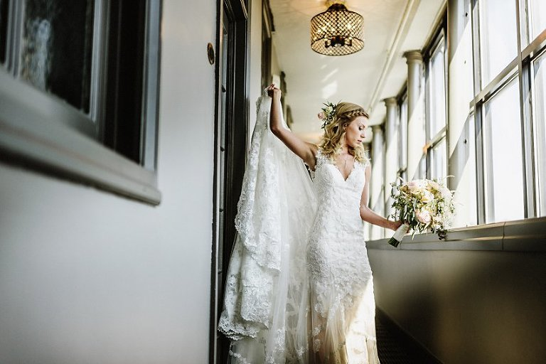 the bride standing in a hallway looking down at her flowers