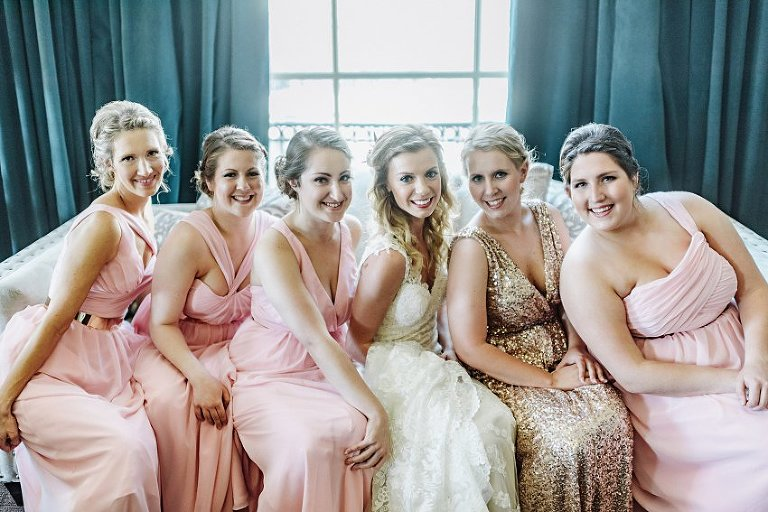 the bride and bridesmaids sitting together on a couch in front of a big window