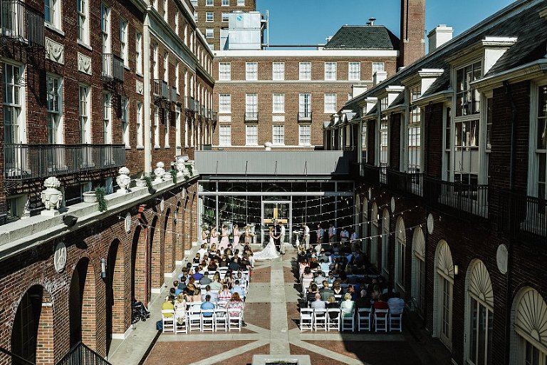 the bride and groom standing in the courtyard at their wedding with all of their guests seated watching them