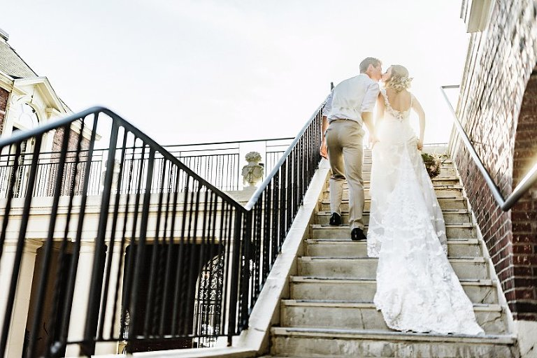 bride and groom exiting up the stairs into the sun while kissing