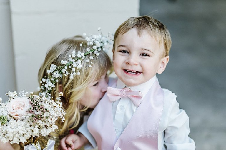 flower girl giving the ring bearer a kiss while he smiles
