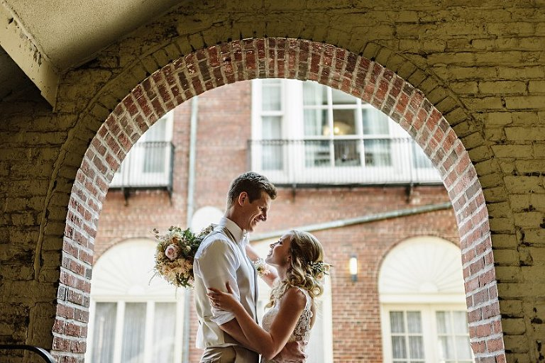 the bride and groom smiling at each other under a brick arch