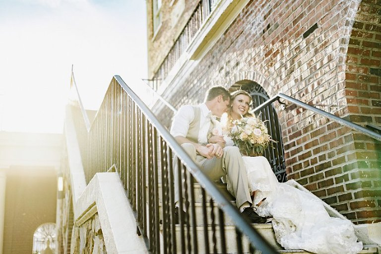 the groom nuzzling the bride's cheek while they sit on the stairs in the sunlight