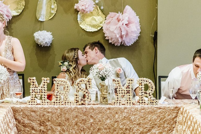 the bride and groom kissing each other at the head table
