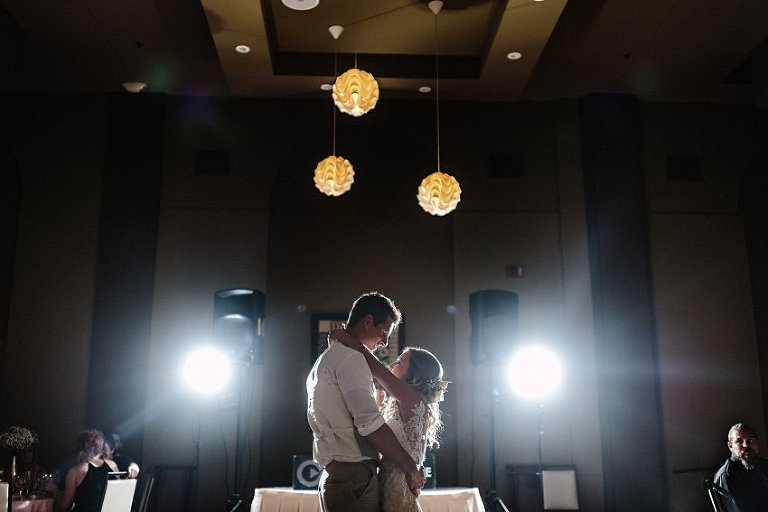 a bride and groom having their first dance in the spotlights