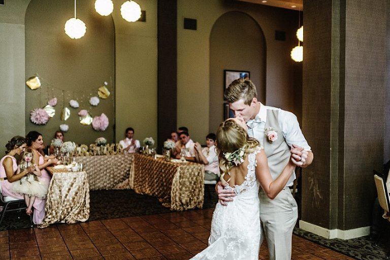 a bride and groom kissing at the end of their first dance