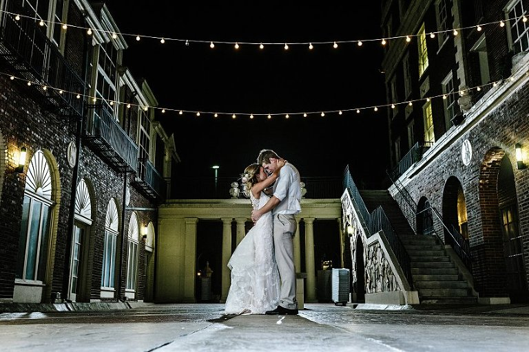 a bride and groom standing in a courtyard at night holding each other close