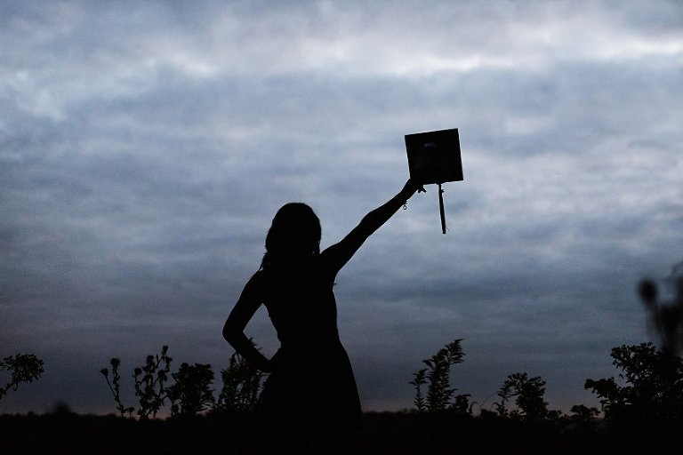 silhouette of a girl holding a graduation cap in the air in front of dark clouds