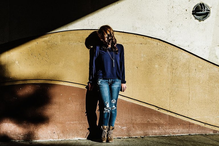 girl in a blue top and jeans standing in front of a decorative concrete wall with a shadow overhead
