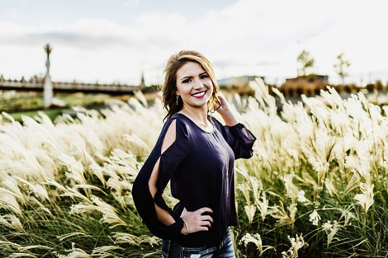 girl in a blue top standing in tall grass while the wind blows