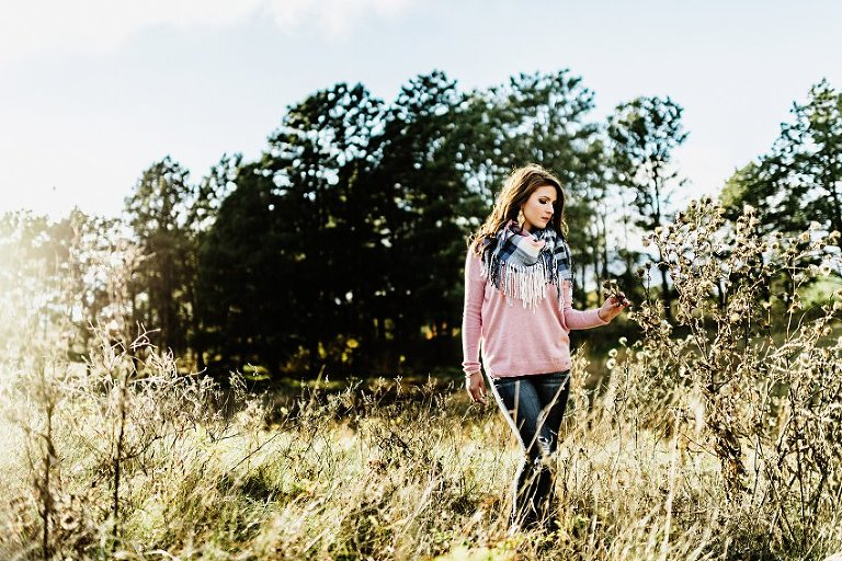 girl in a pink sweater and scarf walking through the prairie and touching the plants