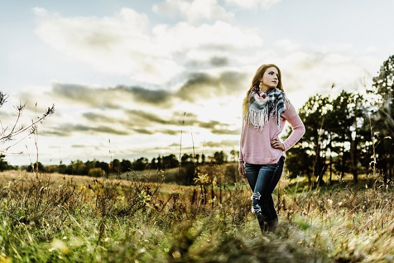 girl in a pink sweater and scarf standing in the prairie grass with a sunset behind her