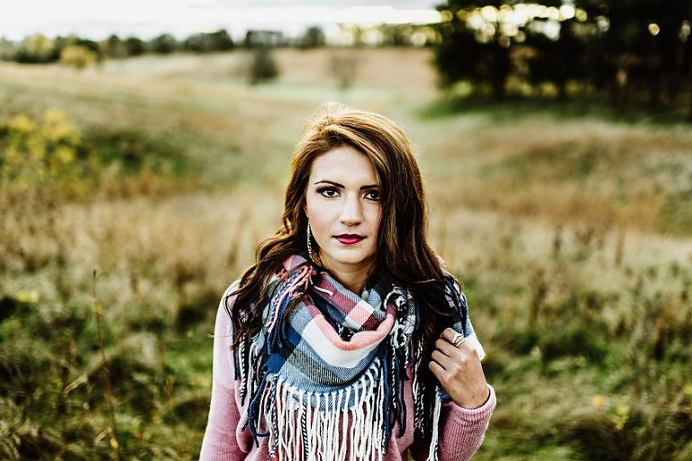 girl in a pink sweater and scarf playing with her hair