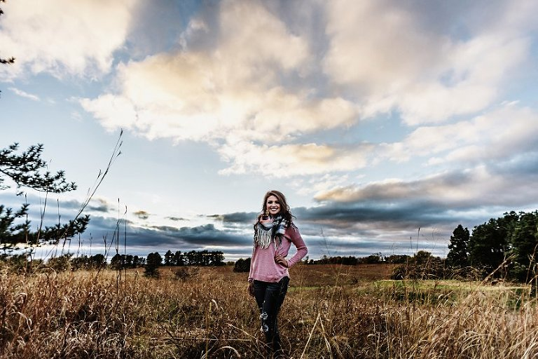 girl in a pink sweater and scarf standing in the prairie with lots of clouds overhead