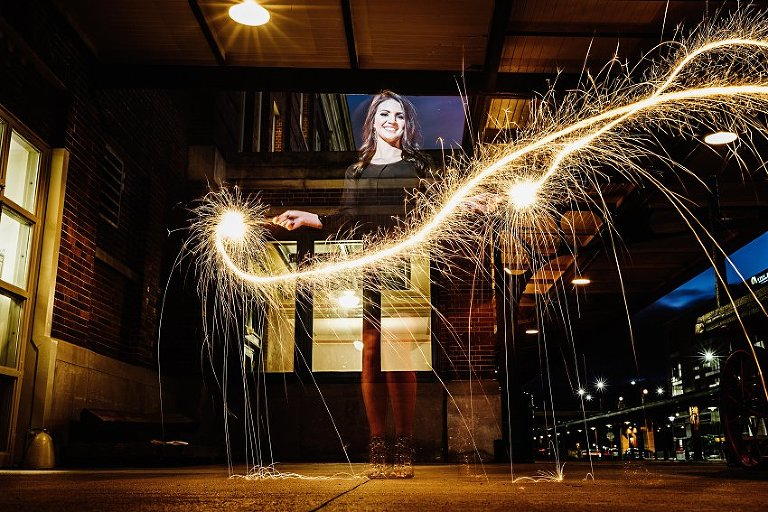 girl in a black dress waving sparklers around as they make light streaks