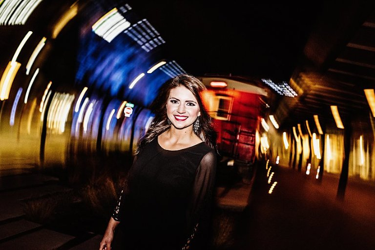 girl in a black dress walking with blurred lights all around her