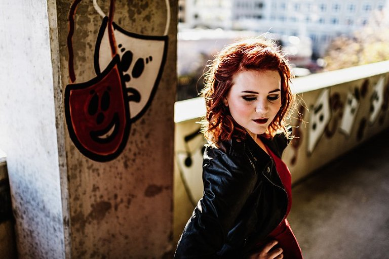 close up of a girl in red top and leather jacket looking down standing in a parking garage with music graffiti in the background